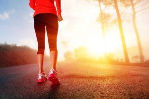 14342135 - athlete runner feet running on road closeup on shoe woman fitness sunrise jog workout wellness concept
