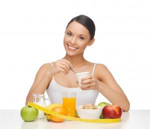18714667 - jovem mulher com café da manhã saudável e fita métrica