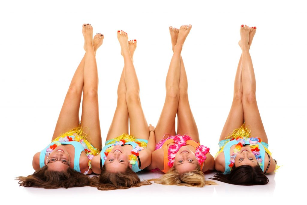 14005704 - a picture of four girlfriends lying on the floor in hawaiian skirts with their legs up over white background