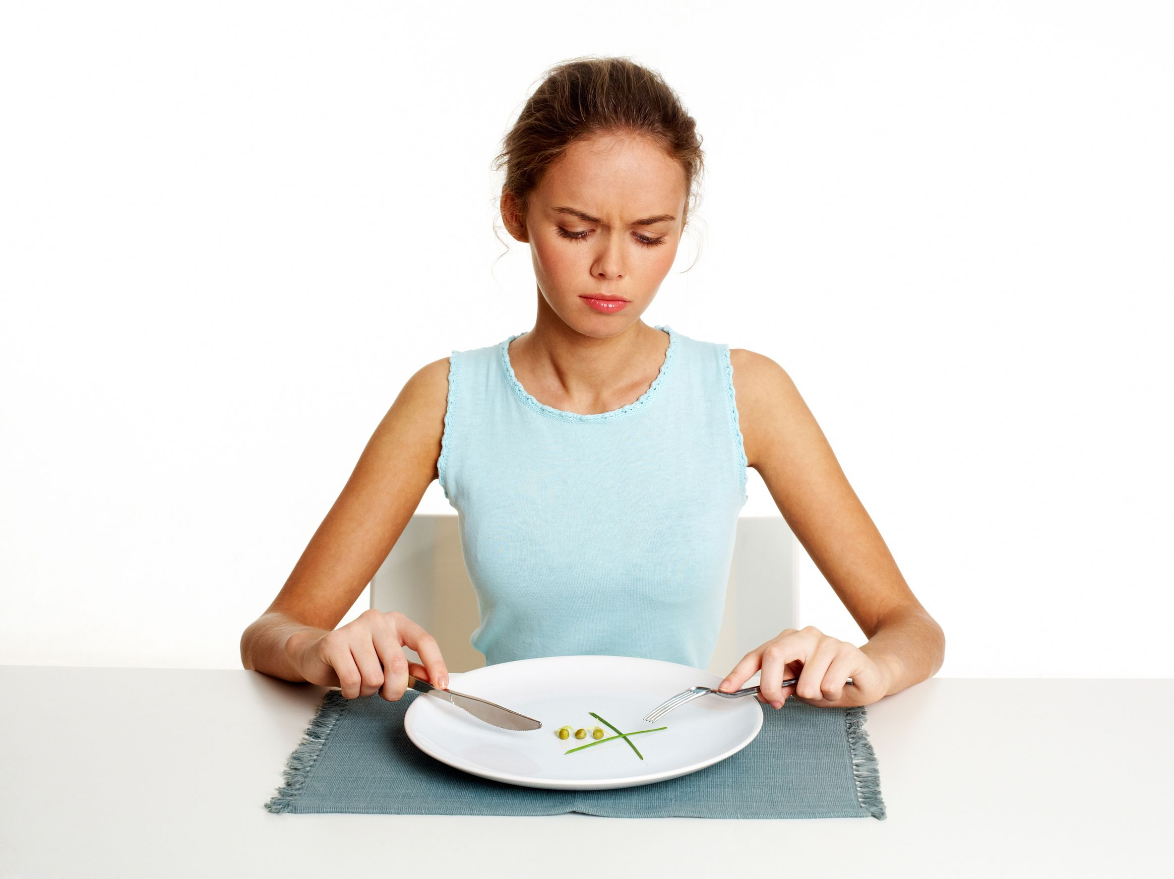 18729434 - unhappy young woman dieting with peas and leeks, isolated against white