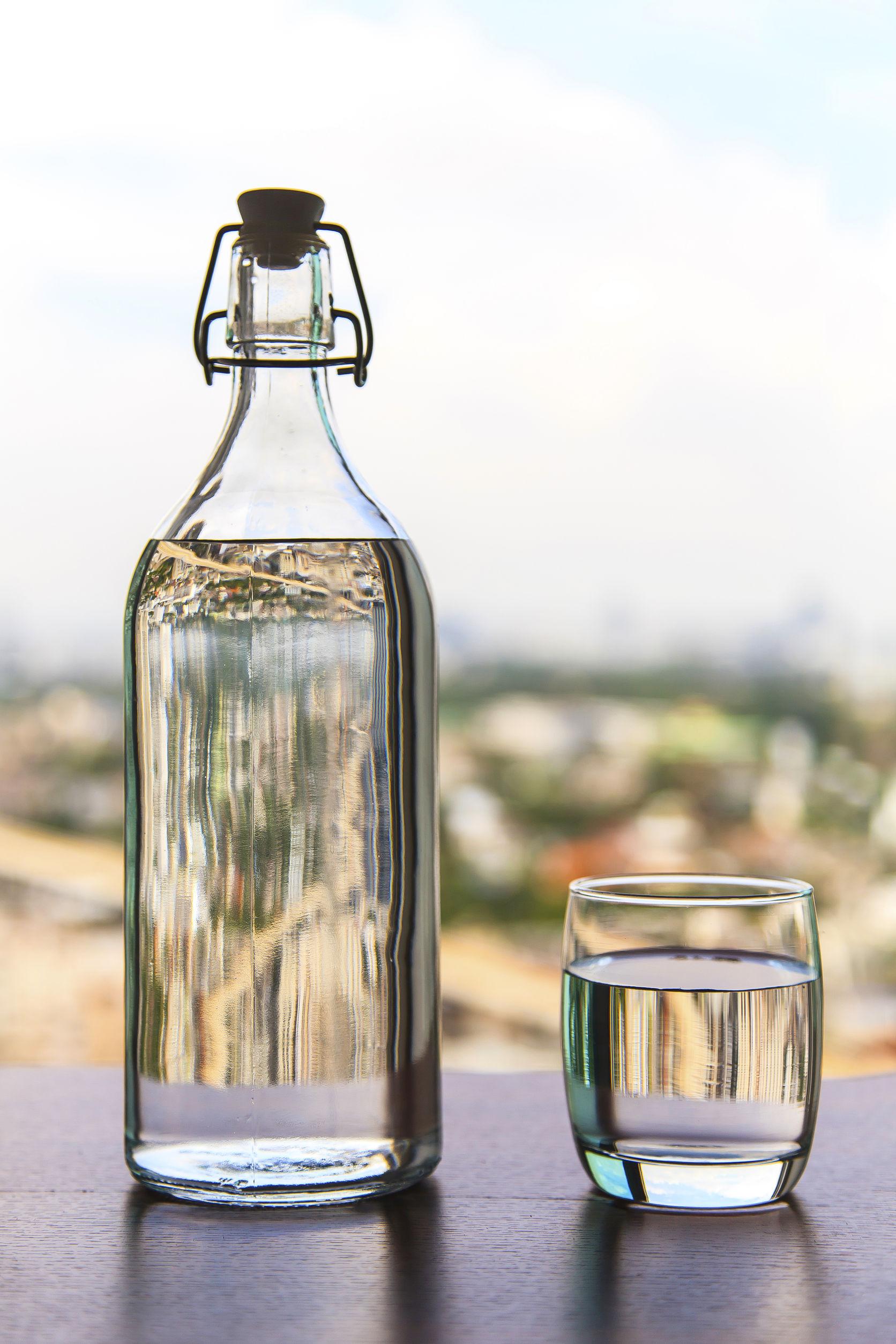 45668068 - copo de água com uma garrafa na mesa
