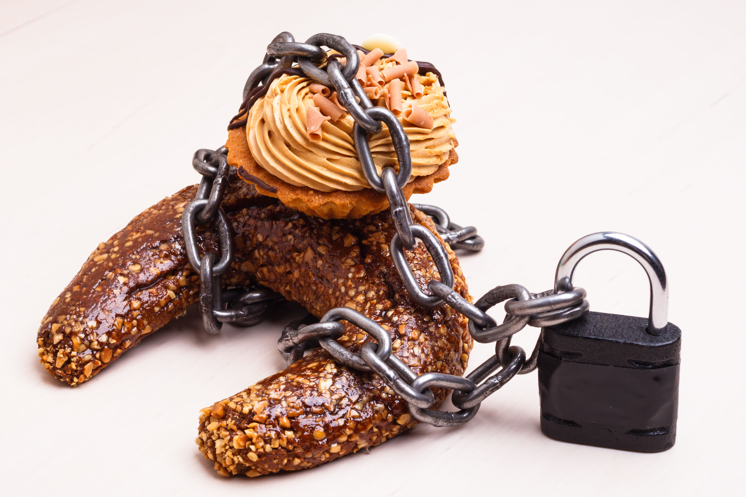 48361056 - diet sugar sweet food addiction concept. cake cupcake wrapped in metal chain and padlock