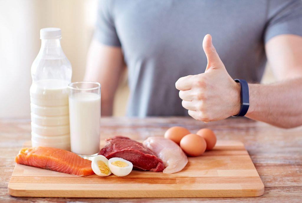 53578415 - conceito de esporte, fitness, estilo de vida saudável, dieta e pessoas - close-up do homem com alimentos ricos em proteínas mostrando os polegares para cima
